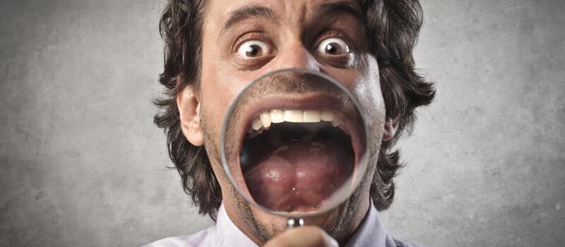 Mann zeigt verzweifelt Zähne